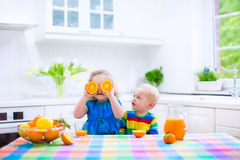 Kids drinking orange juice Royalty Free Stock Image
