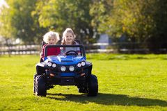 Kids driving electric toy car. Outdoor toys. Kids driving electric toy car in summer park. Outdoor toys. Children in battery power vehicle. Little boy and girl royalty free stock images