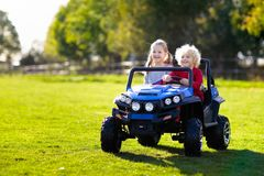 Kids driving electric toy car. Outdoor toys. Kids driving electric toy car in summer park. Outdoor toys. Children in battery power vehicle. Little boy and girl royalty free stock image