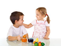 Kids dyeing the easter eggs. Happy kids dyeing the easter eggs - isolated Royalty Free Stock Image