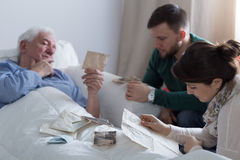 Kids and dying father. Two adult kids sitting with dying father in hospital Royalty Free Stock Photos