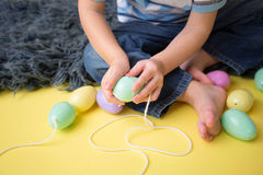 Kids Easter Activity and Crafts. Stringing plastic easter eggs stock image