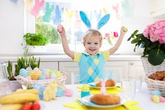 Kids at Easter breakfast. Eggs basket, bunny ears. Royalty Free Stock Images