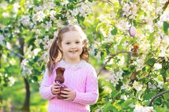 Kids on Easter egg hunt in blooming garden. Royalty Free Stock Images