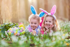 Kids on Easter egg hunt in blooming spring garden. Children with bunny ears searching for colorful eggs in snow drop flower meadow. Toddler boy and preschooler royalty free stock photography