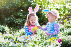 Kids on Easter egg hunt in blooming spring garden. Children with bunny ears searching for colorful eggs in snow drop flower meadow. Toddler boy and preschooler stock photo