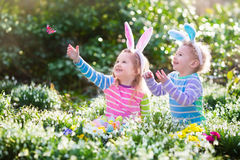 Kids on Easter egg hunt in blooming spring garden. Children with bunny ears searching for colorful eggs in snow drop flower meadow. Toddler boy and preschooler stock image