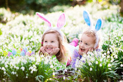 Kids on Easter egg hunt in blooming spring garden. Children with bunny ears searching for colorful eggs in snow drop flower meadow. Toddler boy and preschooler Stock Photos