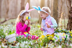 Kids on Easter egg hunt in blooming spring garden. Children with bunny ears searching for colorful eggs in snow drop flower meadow. Toddler boy and preschooler royalty free stock photos