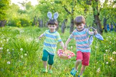 Kids on Easter egg hunt in blooming spring garden. Children searching for colorful eggs in flower meadow. Toddler boy and his brot. Her friend kid boy play Royalty Free Stock Photo