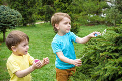 Kids on Easter egg hunt in blooming spring garden. Children searching for colorful eggs in flower meadow. Toddler boy and his brot. Her friend kid boy play Royalty Free Stock Photography
