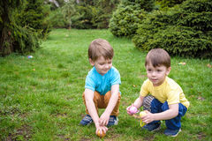 Kids on Easter egg hunt in blooming spring garden. Children searching for colorful eggs in flower meadow. Toddler boy and his brot stock photos