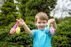 Kids on Easter egg hunt in blooming spring garden. Children searching for colorful eggs in flower meadow. Toddler boy and his brot. Her friend kid boy play Royalty Free Stock Images
