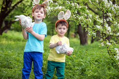 Kids on Easter egg hunt in blooming spring garden. Children searching for colorful eggs in flower meadow. Toddler boy and his brot. Her friend kid boy play Stock Image