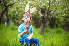 Kids on Easter egg hunt in blooming spring garden. Children searching for colorful eggs in flower meadow. Toddler boy and his brot Stock Photo