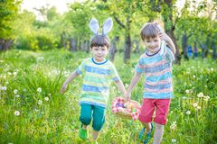 Kids on Easter egg hunt in blooming spring garden. Children sear. Ching for colorful eggs in flower meadow. Toddler boy and his brother friend kid boy play Royalty Free Stock Photos