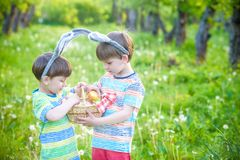 Kids on Easter egg hunt in blooming spring garden. Children sear. Ching for colorful eggs in flower meadow. Toddler boy and his brother friend kid boy play Stock Photos
