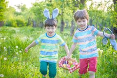 Kids on Easter egg hunt in blooming spring garden. Children sear. Ching for colorful eggs in flower meadow. Toddler boy and his brother friend kid boy play Royalty Free Stock Photography