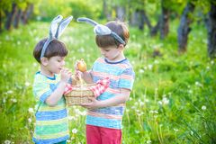 Kids on Easter egg hunt in blooming spring garden. Children sear. Ching for colorful eggs in flower meadow. Toddler boy and his brother friend kid boy play Stock Photo