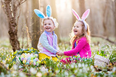 Kids on Easter egg hunt in blooming spring garden. Children with bunny ears searching for colorful eggs in snow drop flower meadow. Toddler boy and preschooler royalty free stock images