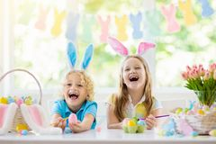 Kids on Easter egg hunt. Children dye eggs. Kids dyeing Easter eggs. Children in bunny ears dye colorful egg for Easter hunt. Home decoration with flowers royalty free stock photography