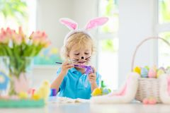 Kids on Easter egg hunt. Children dye eggs. Kids dyeing Easter eggs. Children in bunny ears dye colorful egg for Easter hunt. Home decoration with flowers royalty free stock photos