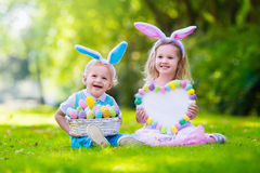Kids on Easter egg hunt. Little boy and girl having fun on Easter egg hunt. Kids in bunny ears and rabbit costume. Children with colorful eggs in a basket royalty free stock photos