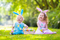 Kids on Easter egg hunt. Little boy and girl having fun on Easter egg hunt. Kids in bunny ears and rabbit costume. Children with colorful eggs in a basket royalty free stock image