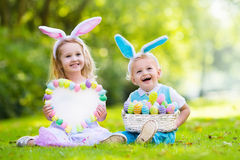 Kids on Easter egg hunt. Little boy and girl having fun on Easter egg hunt. Kids in bunny ears and rabbit costume. Children with colorful eggs in a basket stock photography