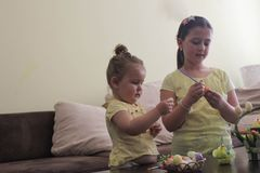 Kids Easter preparation by painting Easter eggs stock images