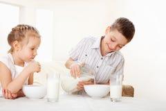 Kids eat breakfast. Children eat breakfast. Family eating cereals with milk Stock Photos
