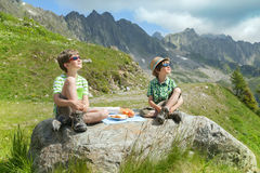 Kids eat cheese and bread on big stone in mountains Stock Photography