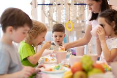 Kids eat at holiday in daycare. Kids eat festival cake at holiday in daycare royalty free stock image