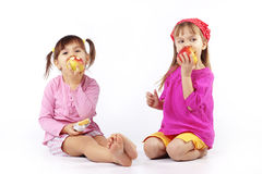 Kids eating apples. Portrait of cute kids eating apples over white stock photo