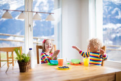 Kids eating breakfast at home. Fruit and milk for children. Children enjoying breakfast in sunny kitchen with big windows. Kids eating fruit cereal and berry royalty free stock image