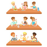 Kids Eating Brekfast And Lunch Food And Drinking Soft Drinks Set Of Cartoon Characters Enjoying Their Meal Sitting At. The Table. Cute Children And Meals They Stock Photos