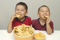 Kids eating chips royalty free stock images