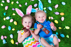 Kids eating chocolate rabbit on Easter egg hunt. Children on Easter egg hunt. Kids eat chocolate rabbit. Boy and girl relaxing on a green lawn in the garden Stock Image