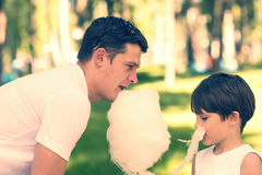 Kids eating cotton candy Stock Images