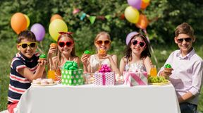 Kids eating cupcakes on birthday party at summer Royalty Free Stock Images