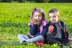 Kids eating donuts Stock Image