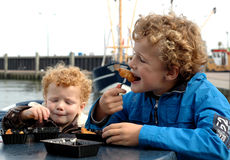 Kids eating fish. Two boys eating fish and chips in a harbour, with a fishing boat in the background Stock Image
