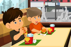 Kids eating hamburger and fries Stock Image
