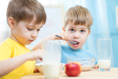 Kids eating healthy food at home or kindergarten. Kids toddlers eating healthy food at home or kindergarten Royalty Free Stock Photo