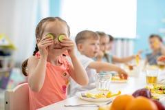 Kids eating healthy food in kindergarten stock photo