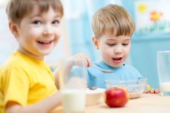 Kids eating healthy food in kindergarten Stock Photo