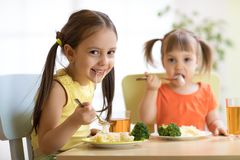 Kids eating healthy food in nursery or at home stock images