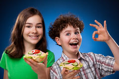 Kids eating healthy sandwiches. Showing OK sign on green background Stock Photos