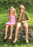 Kids eating ice-cream. Barefoot girl in pink and white dress with ponytales and boy in green t-shirt and shorts sitting eating ice-cream Royalty Free Stock Photography