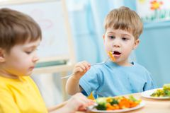 Kids eating in kindergarten. Kids boys eating healthy food in kindergarten or at home Royalty Free Stock Photography